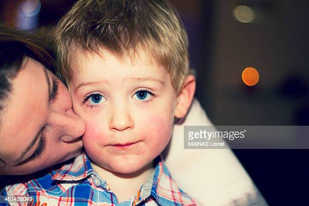 Young boy receiving a kiss for Christmas