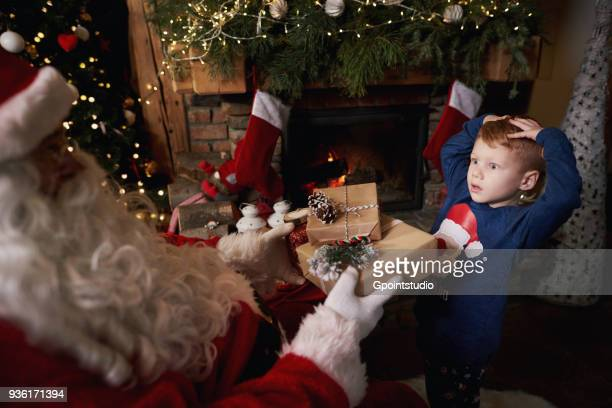 Young boy receiving gifts from Santa