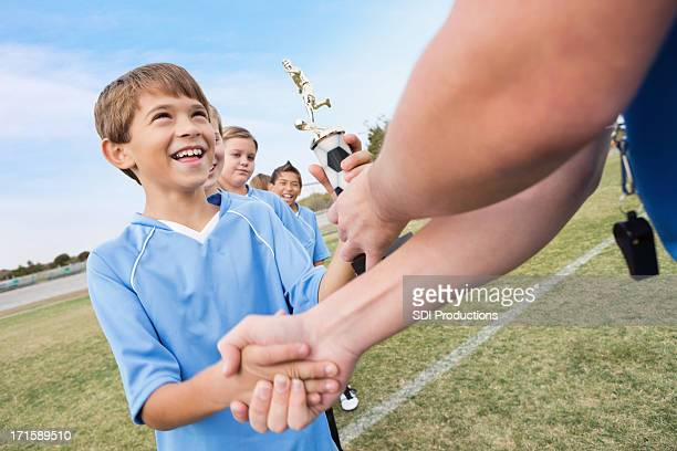 Young boy receiving trophy at sporting event