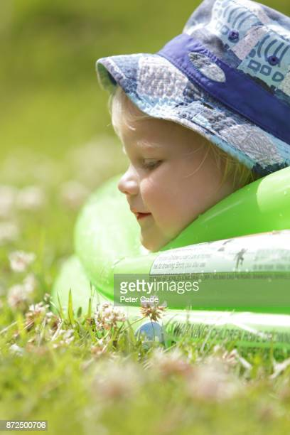 Young boy relaxing in paddling pool in garden