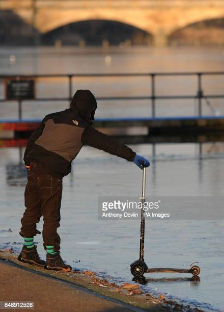 A young boy rests a scooter on the frozen Serpentine in Hyde Park London as parts of Britain were placed on amber alert today as the country lies in...