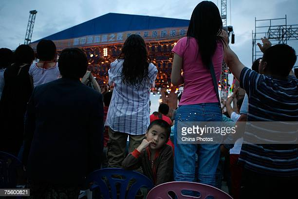 A young boy rests as audience watches the stage at the first 'Green Flag Erdos Grassland Rock Music Festival' near the Mausoleum of Genghis Khan on...