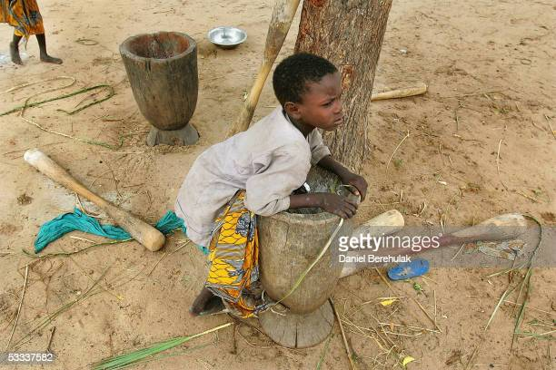 A young boy rests on an empty and unused pestle and mortar in the village of Janguna Abanda on August 7 2005 near Maradi Niger Recent rains have...