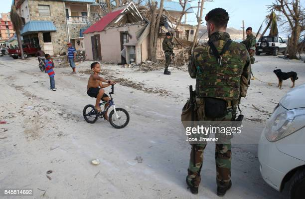 A young boy rides his bicycle as Royal Dutch Marines patrol on September 11 2017 in Philipsburg St Maarten The Caribbean island sustained extensive...