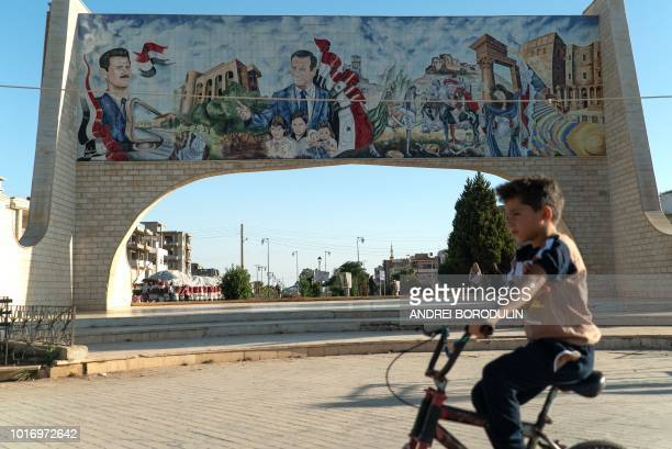 Young boy rides his bicycle in the southern Syrian city of Daraa on August 14, 2018. Behind him is a gate ornated with images of Syrian President...