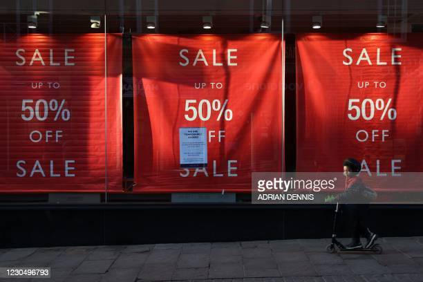 Young boy rides his scooter past the window of a closed department store in Windsor, west of London, on January 9, 2021 as life continues under...