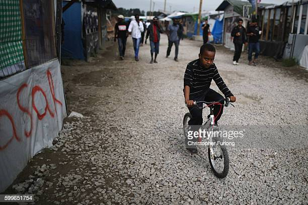 A young boy rides hois bicycle outside the Jungle Books Cafe in the Jungle migrant camp on September 6 2016 in Calais France The dropin cafe for...