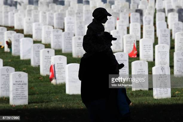A young boy rides on his father's shoulders while visiting Arlington National Cemetery on Veterans Day November 11 2017 in Arlington Virginia...