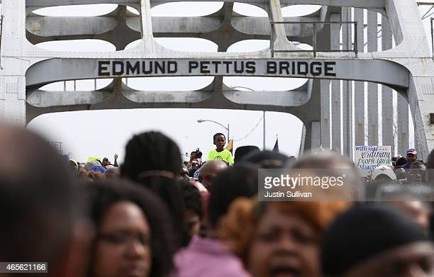 Young boy rides on the shoulders of a parent as thousands of people walk across the Edmund Pettus Bridge during the 50th anniversary commemoration of...