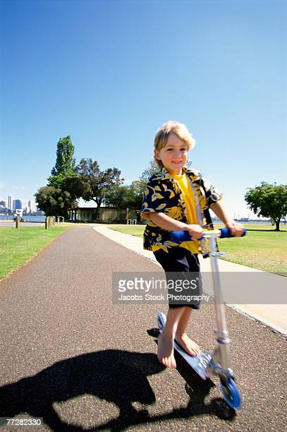 Young boy riding a scooter