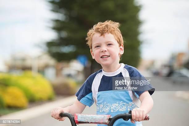 Young boy riding bike on road, Australia