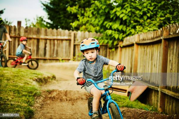Young boy riding BMX bike on backyard dirt track on summer evening