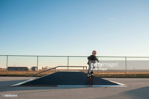 young boy riding down pyramid ramp at the skate park on sunny day - hoverboard stock pictures, royalty-free photos & images