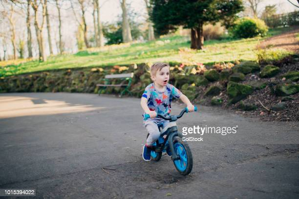 Young Boy Riding his Bicycle Through the Park