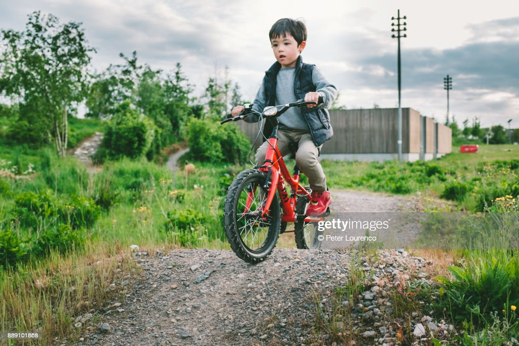 A young boy riding his bike on dirt track : Stock Photo