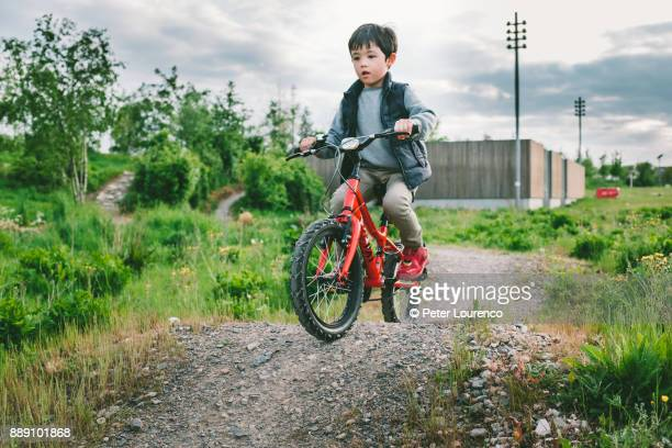 a young boy riding his bike on dirt track - peter lourenco stock pictures, royalty-free photos & images