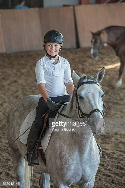Young boy riding horse in training stable
