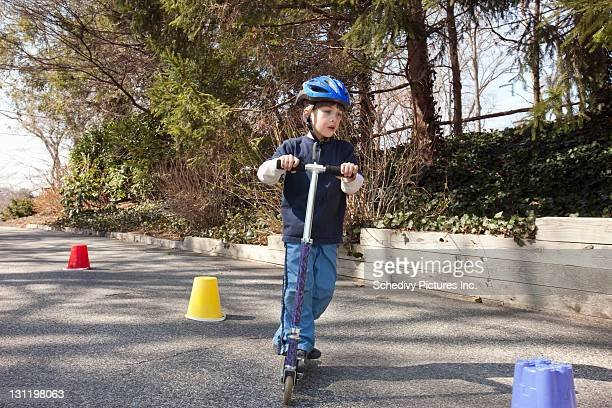 Young boy riding scooter around cones