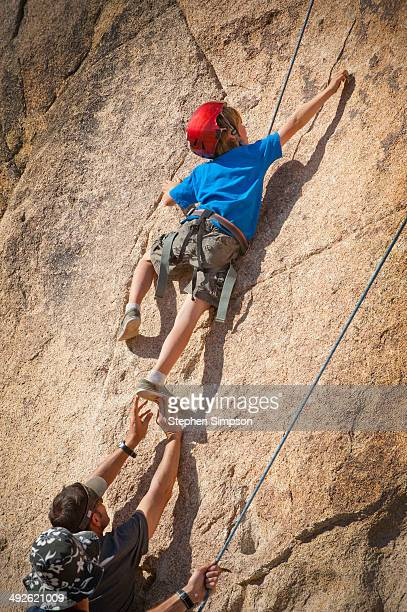 young boy roped in and climbing