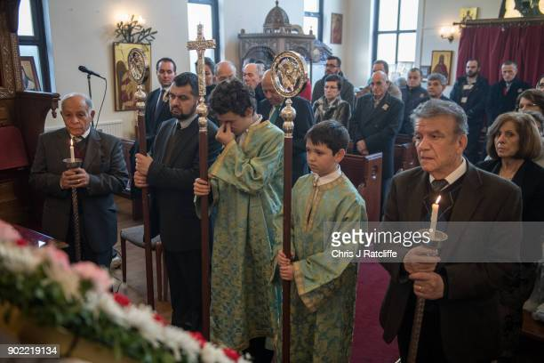 A young boy rubs his eyes during a traditional Greek Orthodox service at the Church of St Michael the Archangel for the Feast of the Epiphany on...