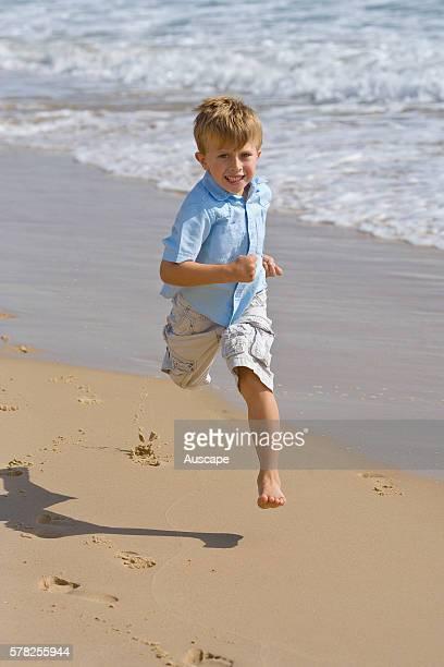 Young boy running along a beach towards the photographer. Mooloolaba, Sunshine Coast, Queensland, Australia.