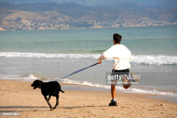 young boy running along the beach of San Juan in Alicante