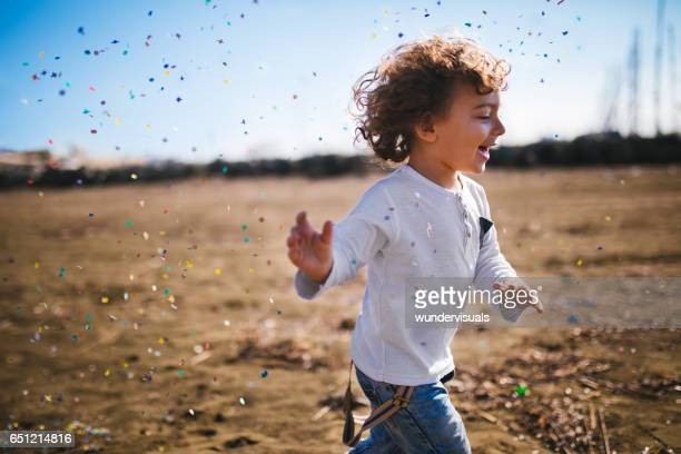 Young boy running at the beach with confetti