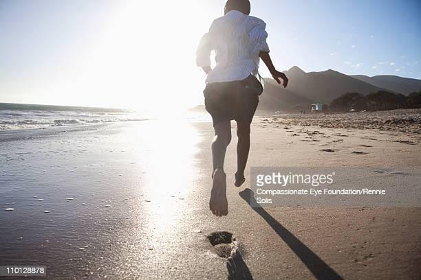 Young boy running down the beach