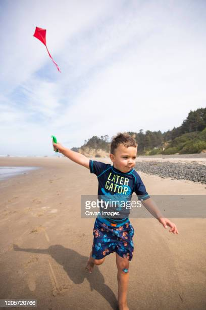 young boy running kite along the beach with determination. - manzanita stock pictures, royalty-free photos & images