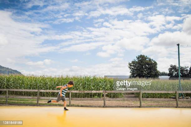 young boy running on large yellow trampoline at rural farm. - big bums stock pictures, royalty-free photos & images