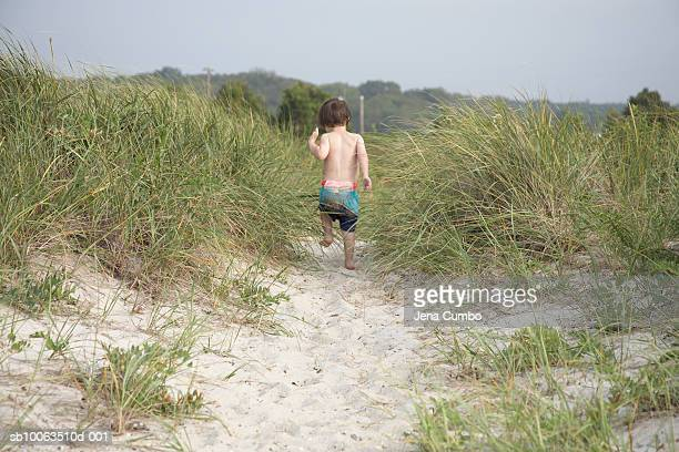 Young boy (4-5) running on sand dune, rear view