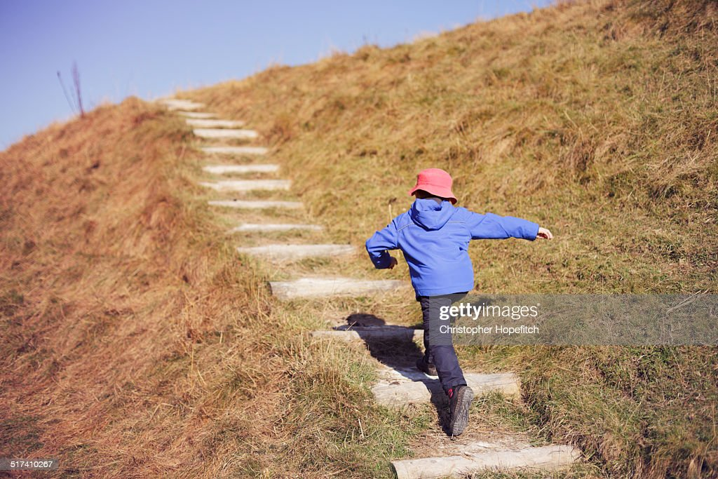 Young boy running up steep path : Stock Photo