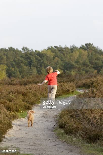 young boy running with his dog at Fischbeker Heide Harburg Hamburg Germany