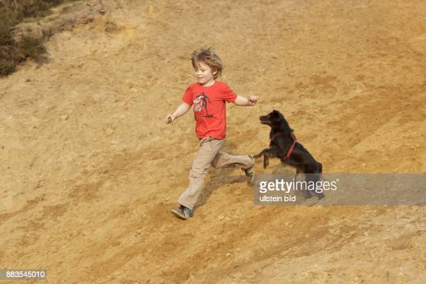 young boy running with his dog down a slope
