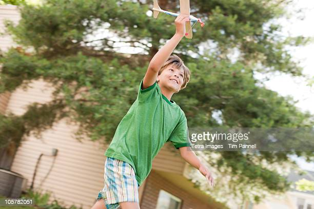 Young boy running with toy airplane