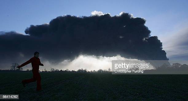 A young boy runs across fields to get a view of plumes of smoke rising from Bruncefield oil depot on December 11 2005 in Hemel Hempstead EnglandThe...