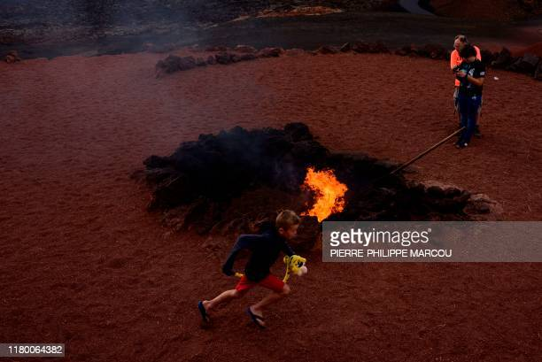 A young boy runs around a fire on the volcanic soil of Timanfaya National Park near Yaiza on the island of Lanzarote in the Canary Islands on October...