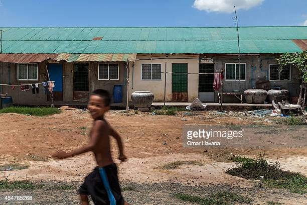 A young boy runs in front of a row of houses in the Tuol Sambo community on September 6 2014 in Tuol Sambo Cambodia Three different communities live...