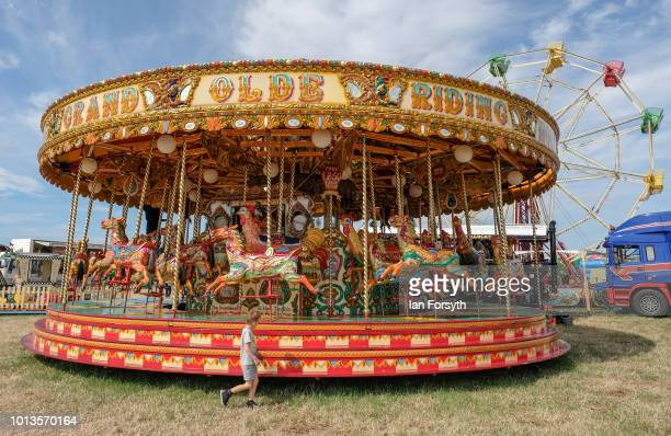 Young boy runs in front of a steam powered carousel during the final day of the Whitby Traction Engine Rally on August 5, 2018 in Whitby, England....