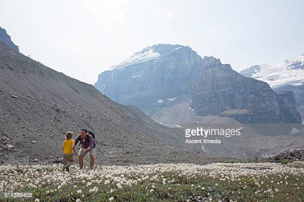 Young boy runs into fathers arms, mountain meadow