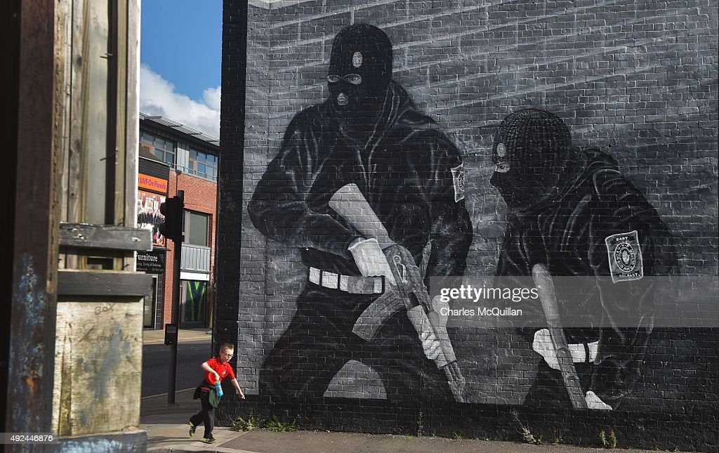 A young boy runs past a loyalist paramilitary mural on the day that the new Loyalist Community Council was launched at the Park Avenue Hotel on October 13, 2015 in Belfast, Northern Ireland. The council has the backing of the three main loyalist paramilitary groups, the UVF, the UDA and the Red Hand Commandos. A joint statement from the three loyalist groups said that they are 're-committing to the principals of the Belfast Agreement' and that they 'eschew all violence and criminality'. The launch of the new loyalist community council comes against the backdrop of an ongoing crisis at Stormont following following allegations that the IRA were involved in the murder of their former member Kevin McGuigan.