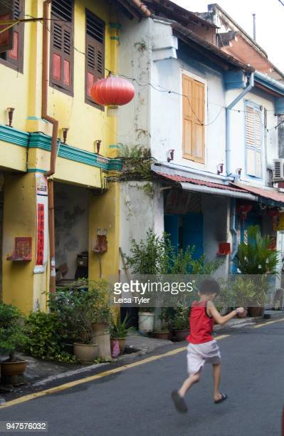 A young boy runs past colourful shop houses known as terrace houses in Malacca Malaysia