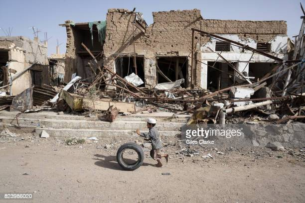 A young boy runs with his tyre past buildings damaged by airstrikes in Saada's Old Town Up until August 2015 this area was home to Saada's oldest...