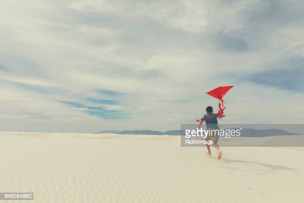 young boy runs with kite at white sands - kite toy stock pictures, royalty-free photos & images