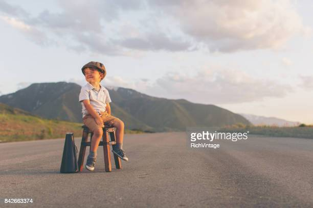 Young Boy Salesman Sits on Stool with Megaphone