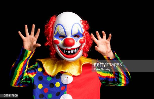 young boy scaring people wearing clown mask - clown stock-fotos und bilder