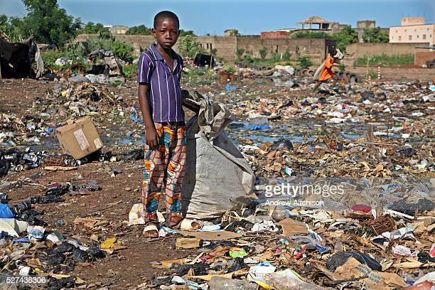 A young boy scavenges through a waste dump looking for anything plastic that he can sell for recycling Bamako Mali