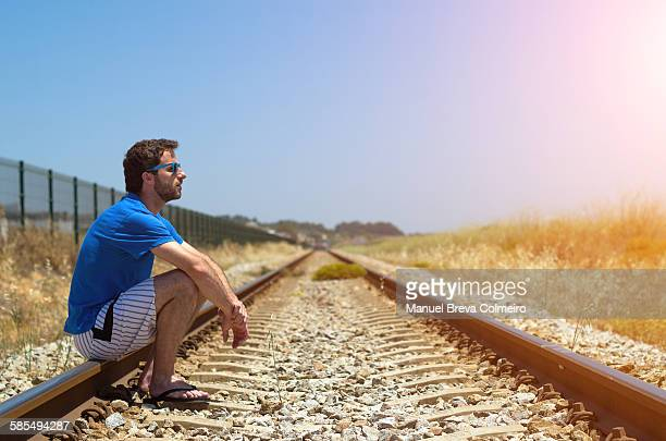 Young boy seated on train tracks