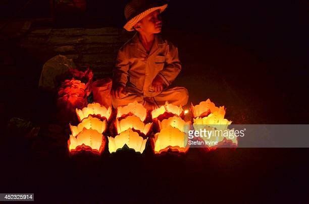 A young boy sells candles as basic lanterns for tourists to buy and release along the river during a festival in Hoi An Vietnam