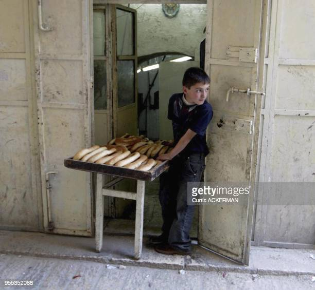 A young boy sells fresh baked bread from the doorway of the bakery in the Muslim Quarter of Jerusalem's Old City The Muslim Quarter derives most of...